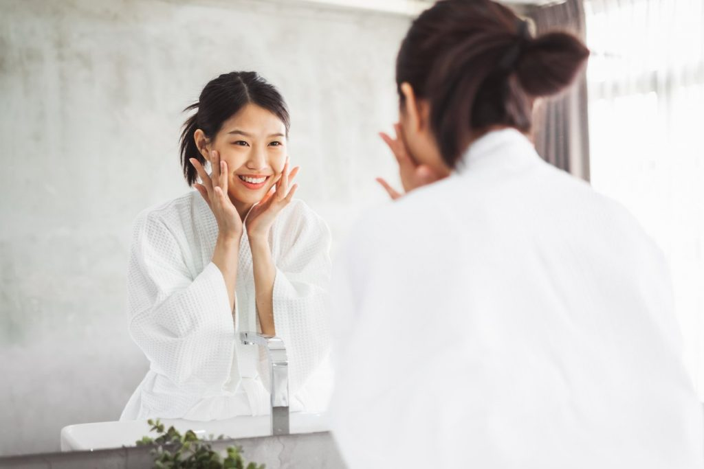 Asian woman cleaning face front of mirror